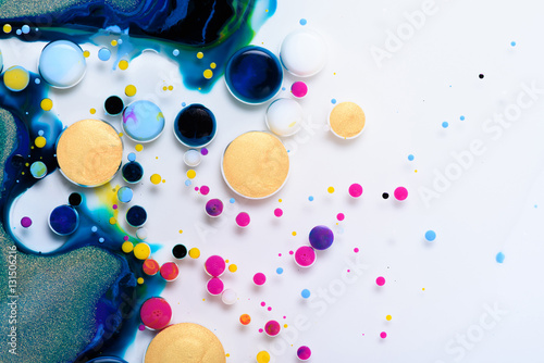 Colorful paint drops mixed in liquid on white background