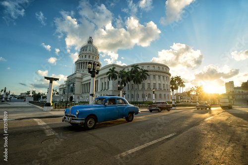 Blue retro car is riding near ancient colonial Capitol building at the center of Havana at sunset