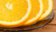 Fragment of orange slices on a glass saucer closeup
