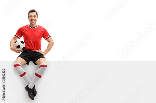 Happy football player sitting on a panel