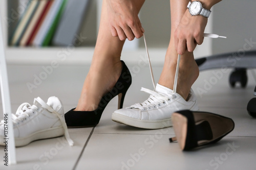 Fotografia  Woman changing shoes in office at work