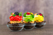 Colorful cupcakes with berries of coffee beans on a wooden background. Focus on the foreground.
