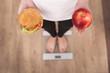 Close up view of woman making choice between apple and hamburger