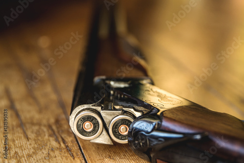 Fotografía  Shotgun charged with bullets and spare bullets on wooden floor,