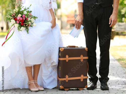 Fotografia  Groom and bride with vintage suitcase on path in park