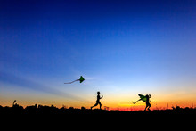 Kid Flying A Kite In Sunset Background
