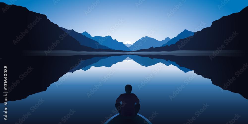 Fototapeta Un homme zen, assis à l'avant d'une barque, médite en contemplant le paysage calme et magnifique d'un lac entouré de montagnes.