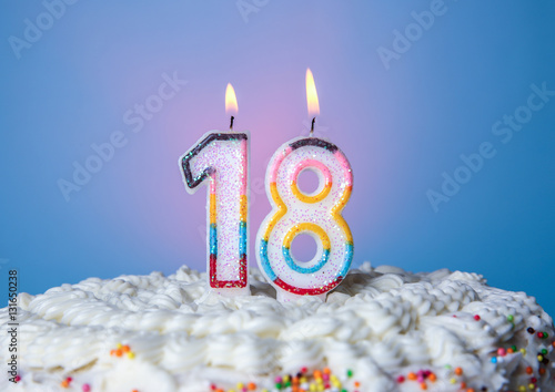 Photographie  Tasty cake with candles for eighteenth birthday on blue background