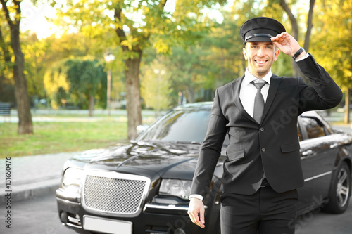 Photographie  Young chauffeur adjusting hat near luxury car on the street