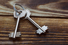 Two Metal Keys On A Wooden Background