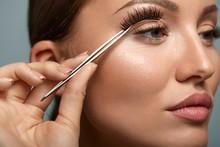 Beauty Makeup. Woman Applying Black False Eyelashes With Tweezer