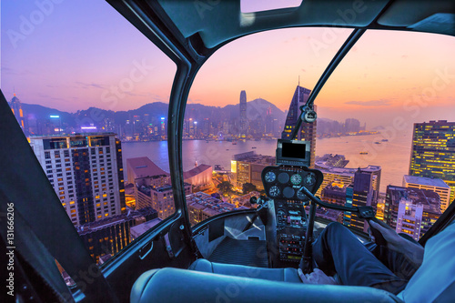 Poster Helicopter Helicopter cockpit flying aerial view of Victoria Harbor, skyscrapers and Hong Kong skyline at night.