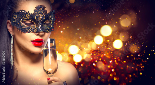 Sexy model woman with glass of champagne wearing venetian masquerade mask Canvas Print