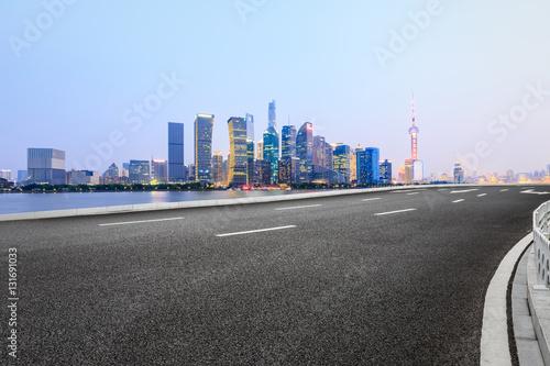 Asphalt road and modern cityscape at night in Shanghai Wallpaper Mural