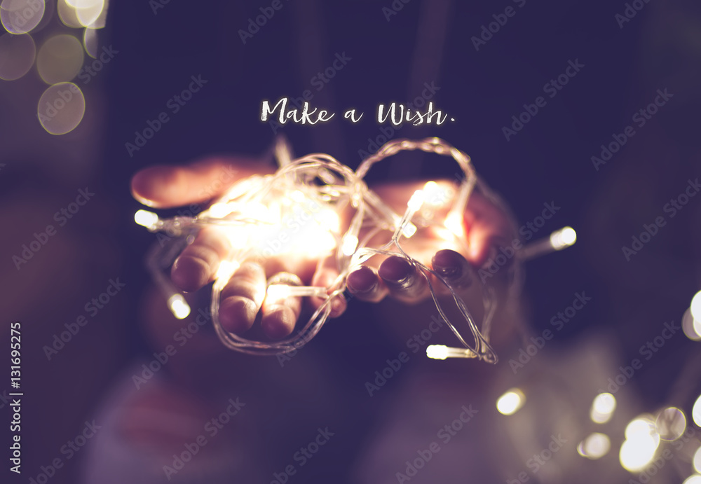 Fototapeta Make a wish word over hand with light bokeh in vintage filter,Ho