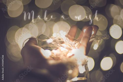 Make a wish word over hand with light bokeh in vintage filter,Ho Billede på lærred