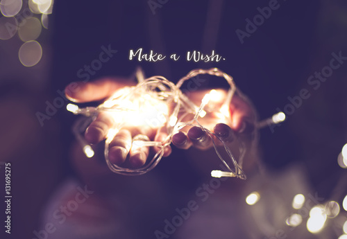 Fotografering  Make a wish word over hand with light bokeh in vintage filter,Ho