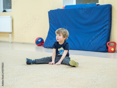 Fotografering  Sports cheerful child doing a set of exercises for stretching