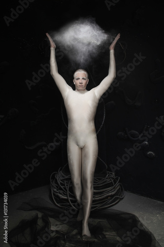 Fotografija dancer in beige spandex jumpsuit posing with flying flour on black background in