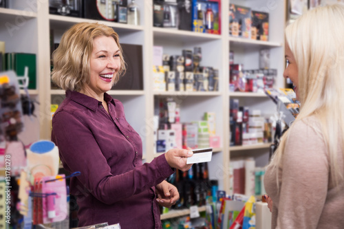Mature seller in cosmetic shop