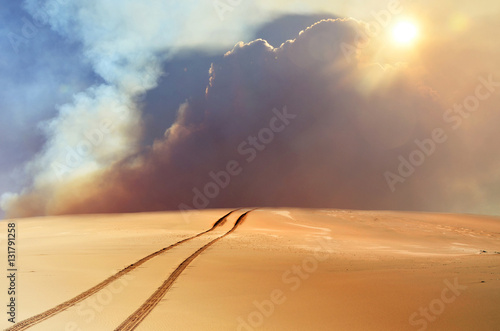 Foto op Aluminium Zandwoestijn Vehicle tracks through desert and dunes leading into a sand, smoke and cloud filled sky.