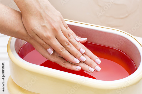 Fotografie, Tablou Process paraffin treatment of female hands in beauty salon