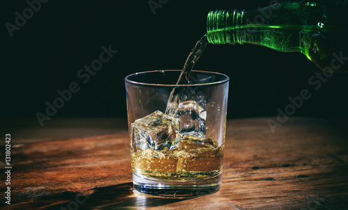 Foto op Canvas Alcohol Pouring whiskey in a glass