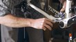 A man tightens the front derailleur on a mountain bike with a screwdriver