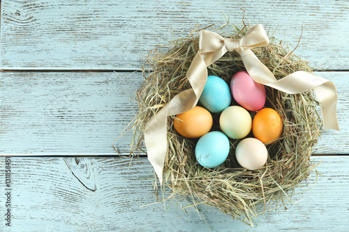 Nest with colorful Easter eggs on wooden table Canvas Print