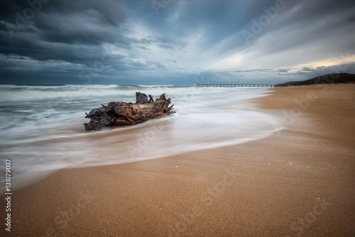 Fotografia  Stormy morning / Stormy sea beach with slow shutter and waves flowing out