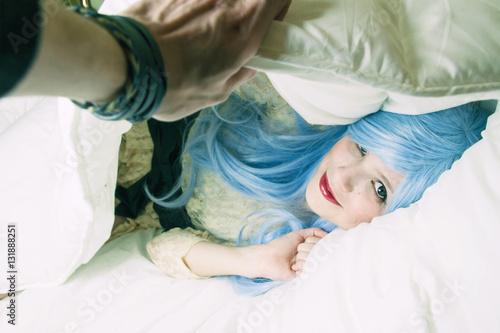 Fotografie, Obraz  Chica joven asomada bajo su edredón mientras su novio la destapa
