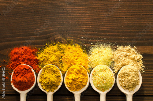 Photo  Spilled powder spices and wooden spoons background