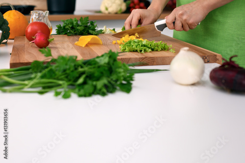 Poster Cuisine Close up of woman's hands cooking in the kitchen. Housewife slicing fresh salad. Vegetarian and healthily cooking concept