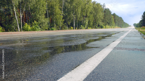 Fotografie, Obraz  View from ground of traffic on wet road, highway with mist splash after rain with green trees on a roadside on background