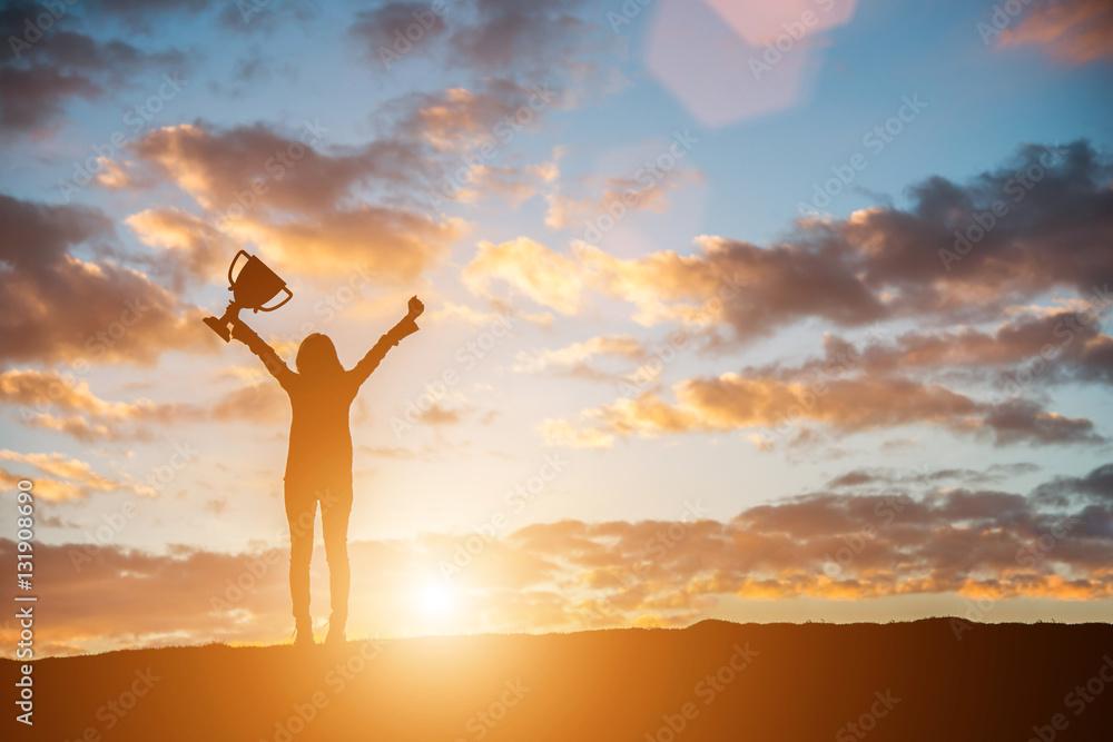 Fototapeta Happy celebrating winning success woman at sunset. Silhouette of