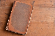Tan Vintage Leather Bound Book Laying On Old Rustic Wood
