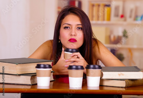 Photo  Young brunette woman wearing pink top sitting by desk holding mug looking tired,