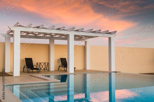 White poolside pergola, gazebo providing shade on a terrace patio area next to an infinity swimming pool at dusk as the sunset turns the sky pinky orange Fototapeta