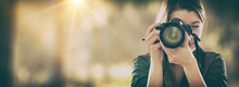 Portrait Of A Photographer Covering Her Face With Camera.