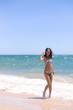 Playful joyful woman with perfect body relaxing feeling free, having fun on tropical beach vacation