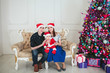 young couple with a baby in a red cap celebrate new year