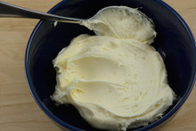 Vanilla Frosting And Spoon In Blue Bowl In Wooden Table