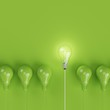 Leinwanddruck Bild - Green pantone light bulbs with glowing one different idea on pastel green background. minimal concept. top view.