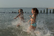 Two young girls have fun and run in the water during the holidays