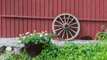 Old Wooden Wagon Wheel Reclining On Red Wooden Wall.Some Flowers In Front.