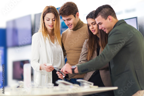 Fototapeta Four people are choosing smart phones in store obraz na płótnie
