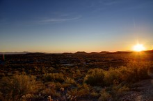 Phoenix, Arizona -  The Sun Setting In The Desert Over Mountains In The Distance.