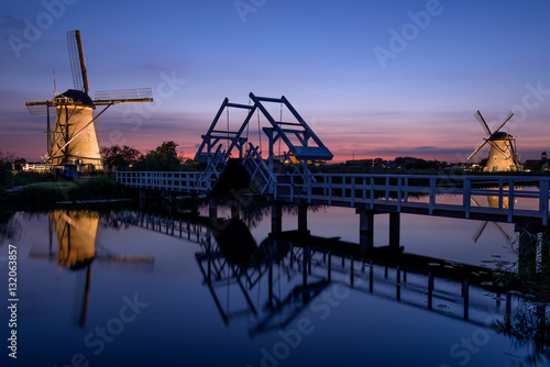 Foto  Illuminated windmills, a bridge and a canal at sunset