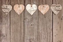 Rustic Birch Bark Heart Ornaments Hanging Against A Vintage Wooden Background