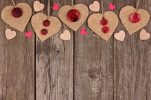 Top Border Of Valentines Day Burlap Hearts With Buttons And Confetti Over A Rustic Wooden Background